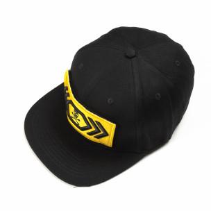 Черна шапка с жълта лепенка